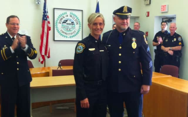 Eva Zimnoch accepts congratulations on being named detective at a ceremony in Wilton on Thursday. Standing with her is her brother Sgt. Lester Zimnoch of the Meriden Police Department. Clapping at left is Interim Police Chief Robert Crosby.
