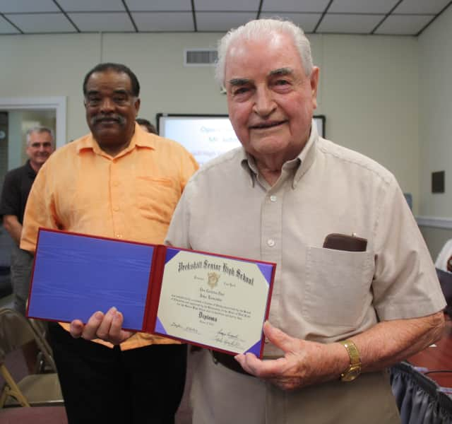 "John ""Jack"" Lancaster displays his high school diploma July 7 after ceremonies at the Peekskill Board of Education meeting as friend Jim Taylor, left, watches."