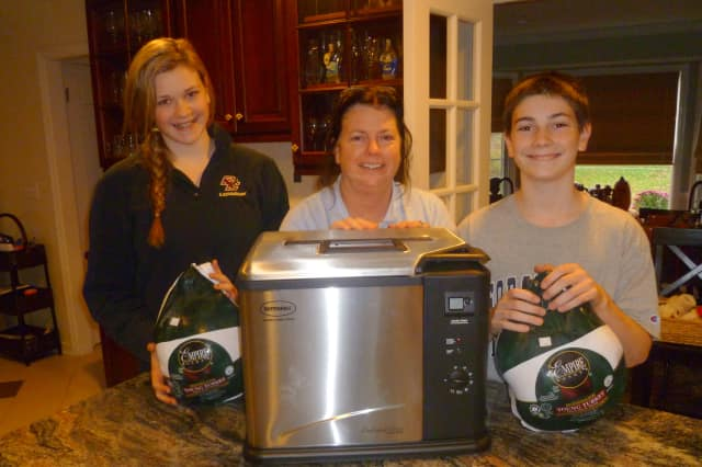 Mary O'Sullivan, flanked by daughter Katie and son Peter, cooked two Thanksgiving turkeys last year, one in the oven, the other in an indoor deep fryer.