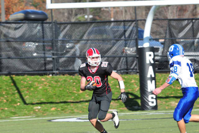 New Canaan freshman Kyle Smith looks to elude a Darien defender during a game last week. New Canaan finished the season 8-0.