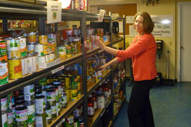 Nancy Coughlin, executive director of Neighbor to Neighbor, stocks the shelves of the organization's food pantry. A $1.5 million gift from the Steven & Alexandra Cohen Foundation will help pay for a new building for food and clothing operations.