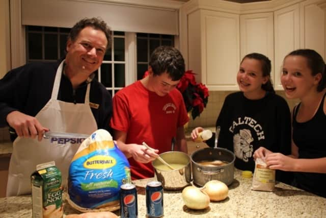 The Craven Family of Wilton prepares for Thanksgiving. Eric Craven, left, is ready to cook the family turkey while siblings David and Amanda Craven prep to make cornbread dressing. Their sister Elizabeth, far right, is opening the Polish Barley.