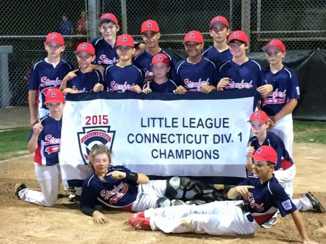 Stamford North Little League players celebrate with the Division 1 banner after beating Fairfield American on Sunday night.