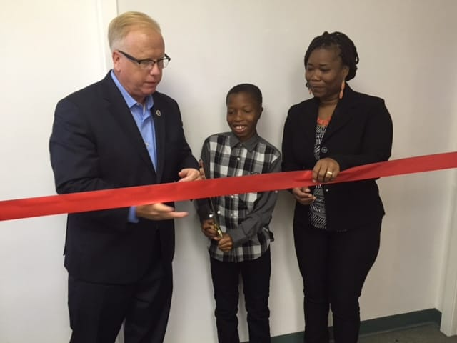 Celebrating the new business by cutting a shiny red ribbon are Danbury's Mayor Mark Boughton; J'quan Barzey (son of the owner); and business owner Nasheba Barzey.