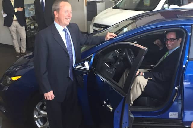 Leo Karl III of Karl Chevrolet in New Canaan (standing) and State DEEP Commissioner Robert Klee (sitting) check out a 2016 Chevrolet Volt while promoting a new state rebate program encouraging drivers to buy electric and hybrid vehicles.
