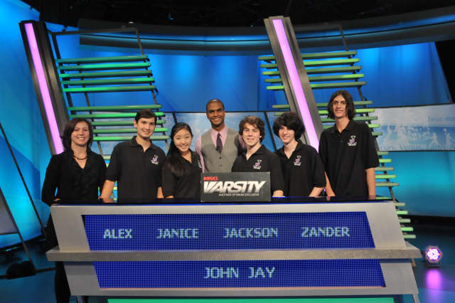 "The John Jay students competing on ""The Challenge"" are, Alex Lee, Janice Choi  (alternate), Jackson Ruzzo (captain), Alexander Bolgar, and Angelo Angelino. At left is academic adviser Vicky Weiss and at center is ""The Challenge"" host Jared Cotter."