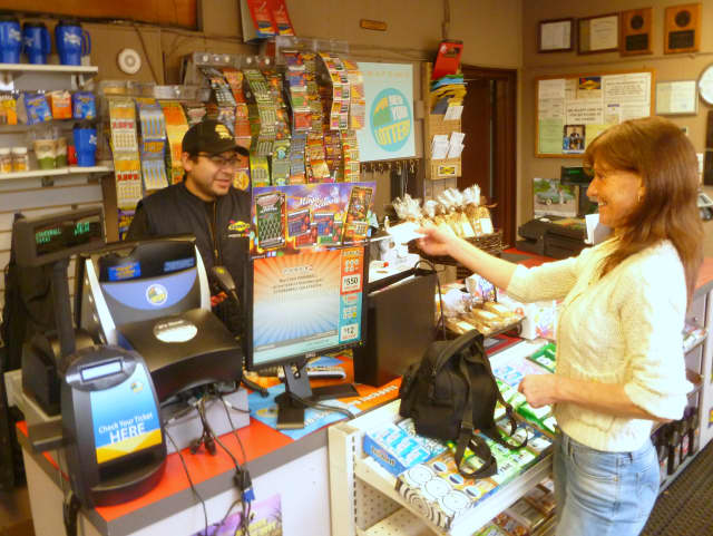 Beth Mulleavey buys a Powerball lottery ticket at Pound Ridge Sunoco on Wednesday afternoon.