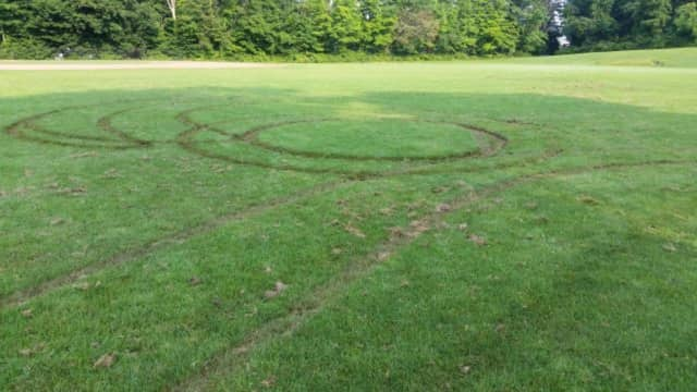 The Ridgefield Police Department charged two men with damage done to the playing fields at East Ridge Middle School.