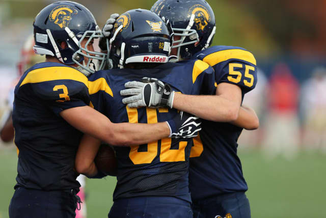 Weston's Jimmy Brasco (55) celebrates with Aaron Pomerance (3) and Thomas McGlone after McGlone caught a touchdown pass in a win over Stratford.