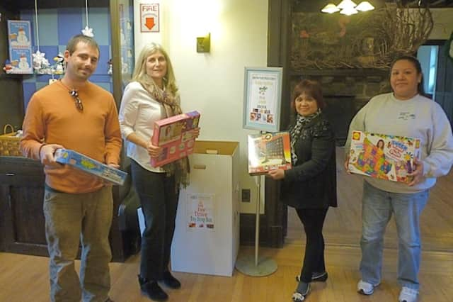 Greenburgh Nature Center employees hold up donated games and toys at their drop-off box on 99 Dromore Road, Scarsdale.