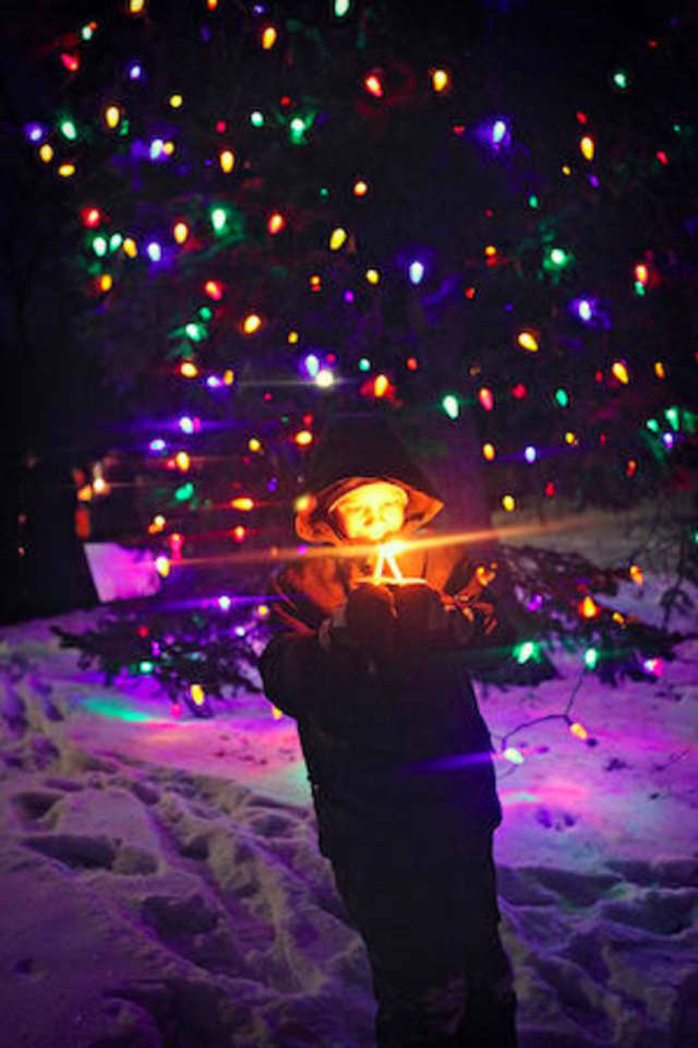A boy holds a candle in front of the tree lit up by the Edgemont Association at Crane's Pond in 2009. Edgemont will hold a tree- lighting ceremony this Sunday.