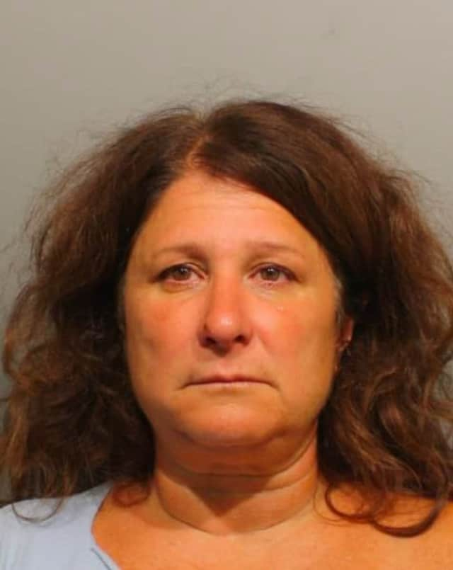 Laura M. Garbuz, 50, of 45 Breeds Hill Place, Wilton, was arrested Monday on a warrant in connection with the theft of an SAT test booklet in June from Wilton High School.