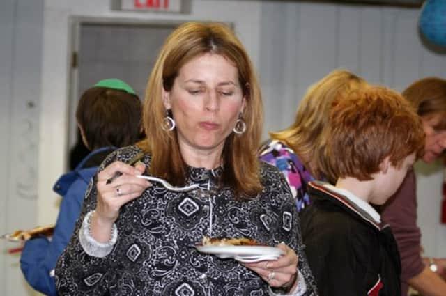 Diane Karsch tastes a latke at the Hebrew Congregation of Somers' annual Latkepalooza.