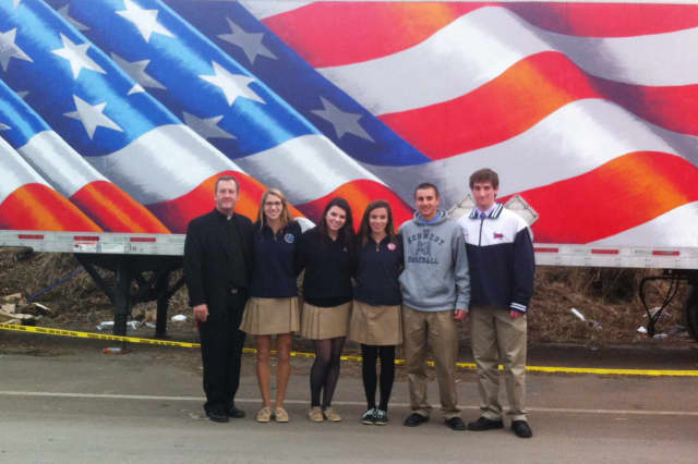 Father Mark Vaillancourt, president and principal of Somers' Kennedy Catholic, poses with seniors Gabrielle D'Amato, Shannon Spillane, Natalie Burke, Ryan Empson and John Brabazon at the VFW relief center.