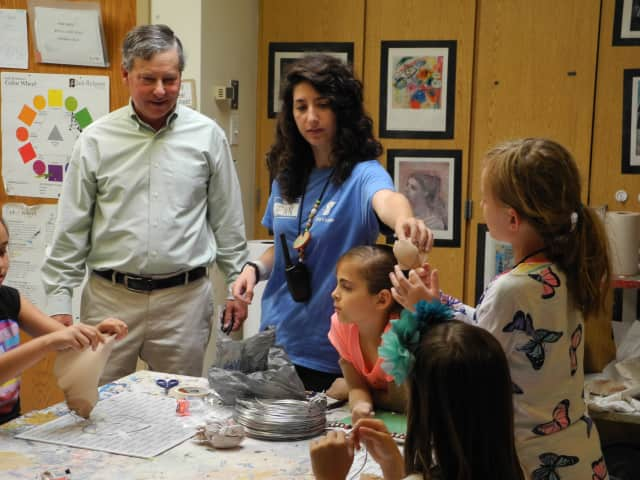 State Assemblyman Steve Otis, a Democrat from Rye, meets with camp counselor Jennifer Cacciola and members of her group during a recent visit to the Rye YMCA's summer camp at Osborn Elementary School.