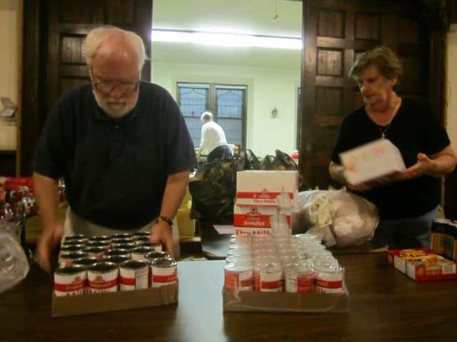 Volunteers Richard Devir Margaret Young prepare food items in September for the Ossining Food Pantry. The pantry is one of several in Ossining and Briarcliff Manor receiving goods through fundraisers this holiday season.