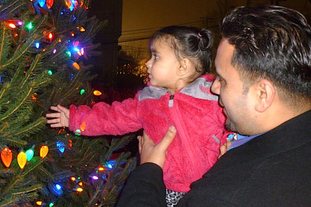 Geet Dhanoa reaches out to touch the Christmas tree at Elmsford Village Hall as her father Rummy holds her.