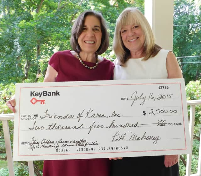 Kathy Gregory, Vice President, KeyBank, presents the grant award to Judith Factor, Friends of Karen Executive Director.