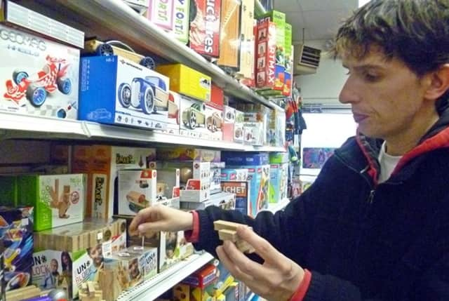 Ridgefield Toy Chest manager Danny Cavanagh shows one of the store's more popular building blocks, the UnBlock.