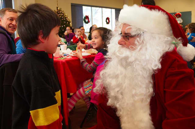 A child at last year's Breakfast with Santa event tells Santa what he wants for Christmas.