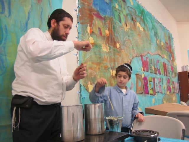 "Rabbi Dovid Labkowski and son Menachemn make candles at Chabad at Briarcliff's ""Dreidel Island"" in Ossining."