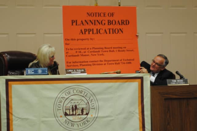 Supervisor Linda Puglisi and town attorney Tom Wood hold a planning board application sign.