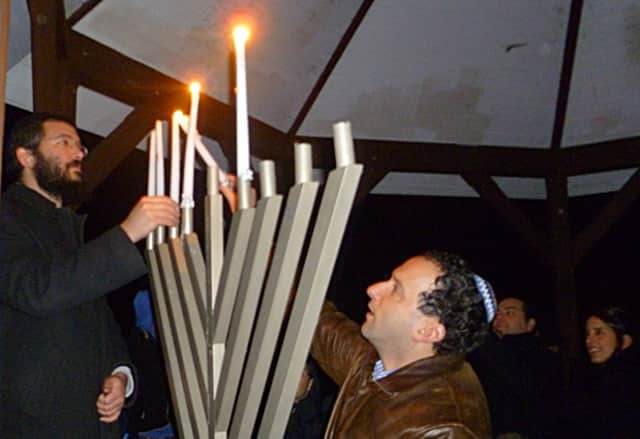 Rabbi Sholom Deitsch of Chabad of Ridgefield and  Rabbi Eric Eisenkramer of Temple Shearith Israel in Ridgefield light the Chabad menorah together at the gazebo in Ballard Park.