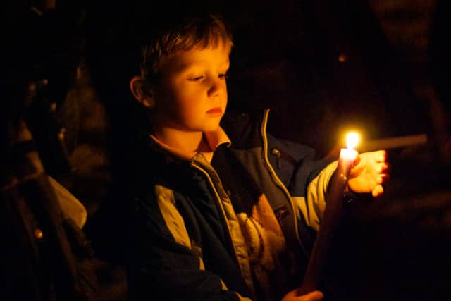A boy holds a candle at a vigil for the shooting at Sandy Hook Elementary School in Newtown, Conn.