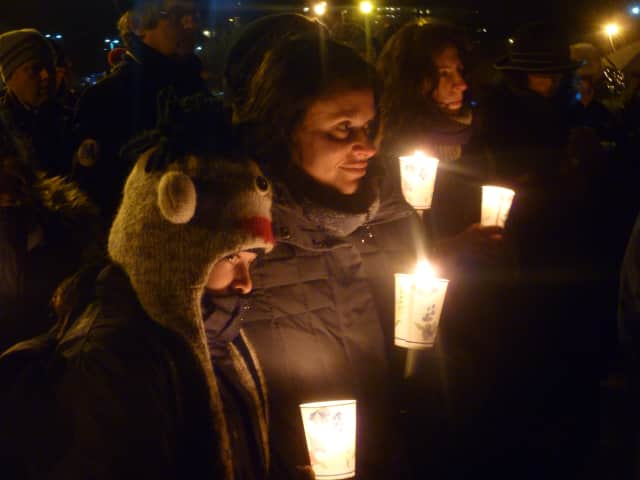 Dobbs Ferry's Juli Klein and her daughter, Ashley, 11, honor the victims of the Newtown, Conn., school shooting during a  candlelight vigil Sunday in Waterfront Park in Dobbs Ferry.