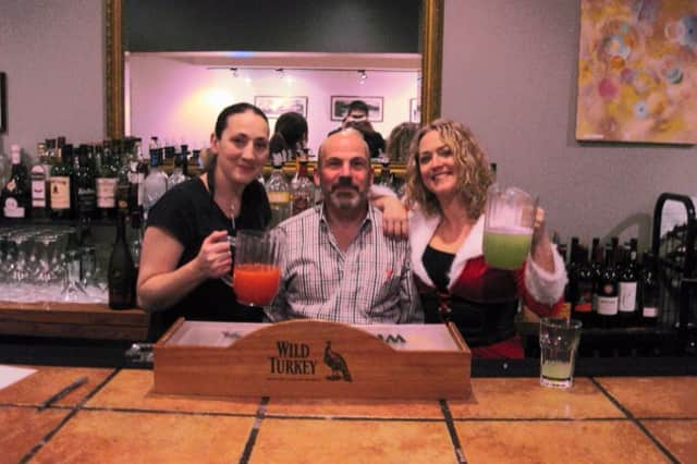 Bartenders Laura Hinkley, left,  Shay Kilby, right, joined Division Street Grill owner Arne Paglia at the bar before SantaCon crawlers arrived.