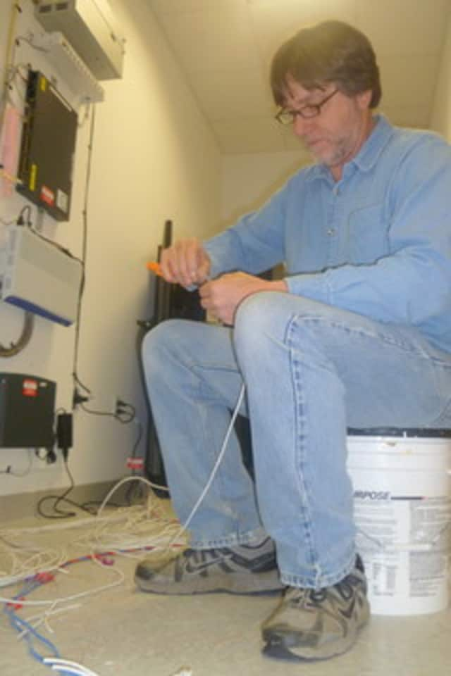 Lewisboro Maintenance Director Joel Smith works on the telephone connections for the new town offices in Cross River.