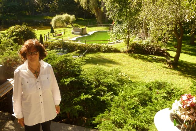 Millie Mendelson poses in her backyard, which she says has become uninhabitable due to stray electrical current from NYSEG.