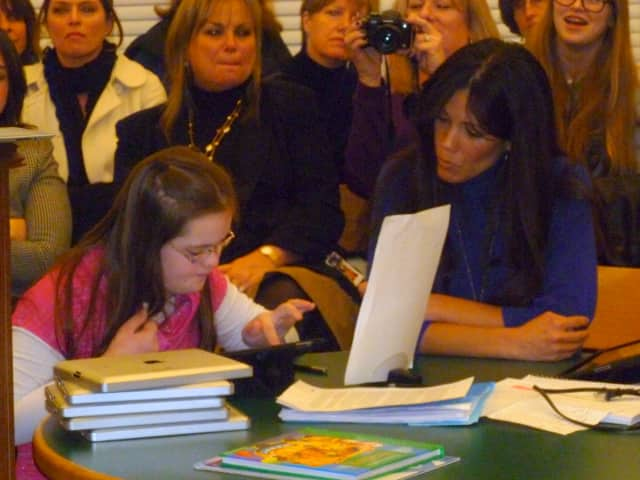 Increase Miller Elementary School student Kaycie Rooney, left, with the help of her teacher Allison Emig, demonstrates to the Katonah-Lewisboro school board how the iPad has helped increase learning in the special education classroom.