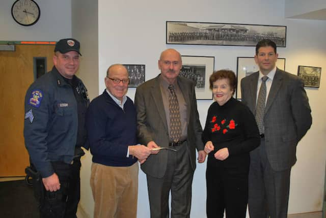 From left, Sgt. Anthony McVeigh of Special Operations, Alan Waxenberg, Greenburgh Police Chief Joseph DeCarlo, Natalie Robinson and Capt. Christopher McNerney of the Detective Division with a $9,000 check from the Metropolis Country Club.