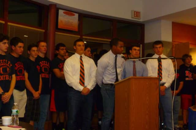 Horace Greeley High School football captain Teddy Graves (at lecturn) was joined by teammates in support of coach Bill Tribou at a Board of Education meeting May 1.