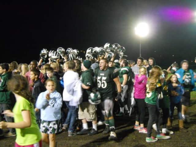 Pleasantville High School football fans congratulate their players after a playoff win.