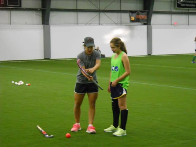 U.S. Olympic field hockey player and Lakeland graduate Melissa Gonzalez, left, works with a field hockey player during the Stars and Stripes Field Hockey clinic at the House of Sports.
