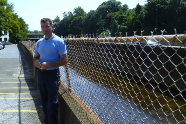 Ladovik Tinaj, assistant superintendent of the Yonkers complex, stands next to the flood barrier residents want to increase to 9.4-feet.