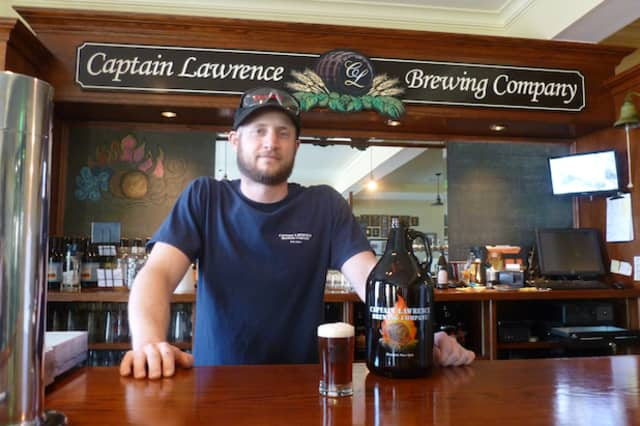 """Ryan Kipp, a brewer at Captain Lawrence Brewing Company, stands with a sample of his new beer called """"The Pride of Elmsford."""""""