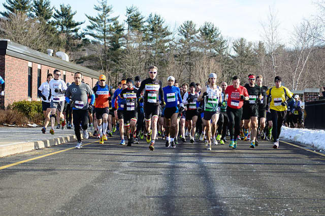 Runners leave the starting line at the start of the Boston Buildup 15k run Sunday in Ridgefield.
