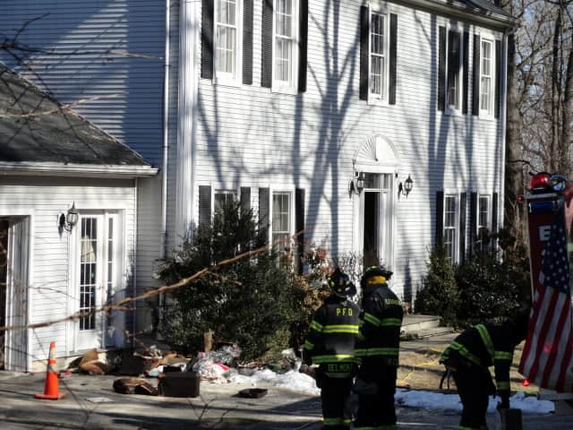 Members of the Pleasantville Fire Department assess the damage done at the Chestnut Street home.