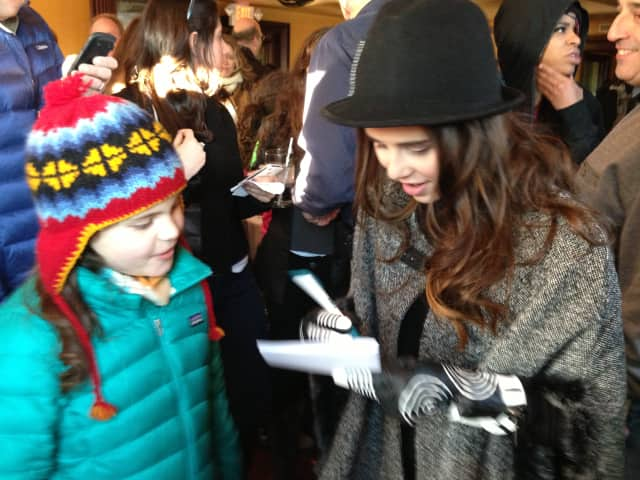 Carly Rose Sonenclar signs an autograph for a young fan at her parade after-party Sunday.