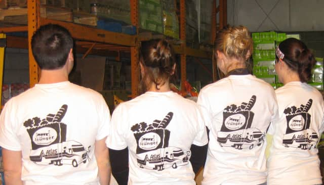 People working at a Move for Hunger food drive show off their shirts.