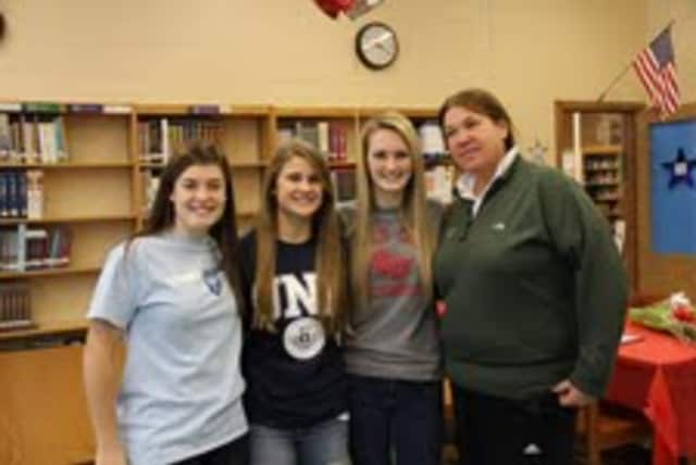 Lakeland field hockey players, from left, Rebbeca Bard, Gianna Bensaia and Kristen Conroy, along with coach Sharon Sarsen after signing their national letters of intent Wednesday.