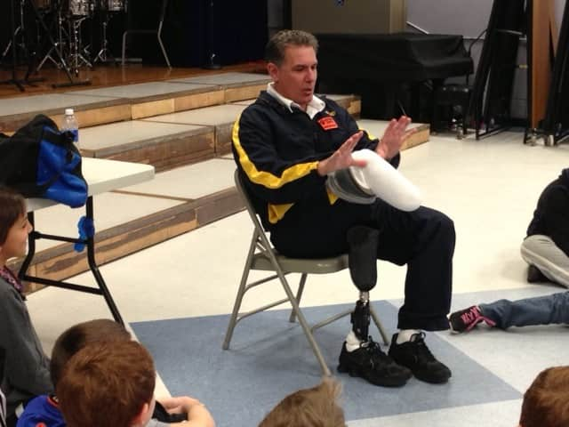 Dennis Oehler makes a moose with his hands and his amputated leg for fourth-graders.