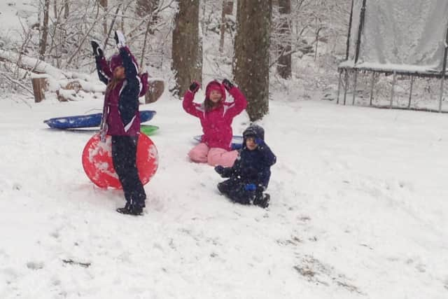 The Ongley siblings Caitlin, 7, Melissa, 6, and Blake, 4, enjoy some sledding fun in the backyard of their Wilton home on Friday.