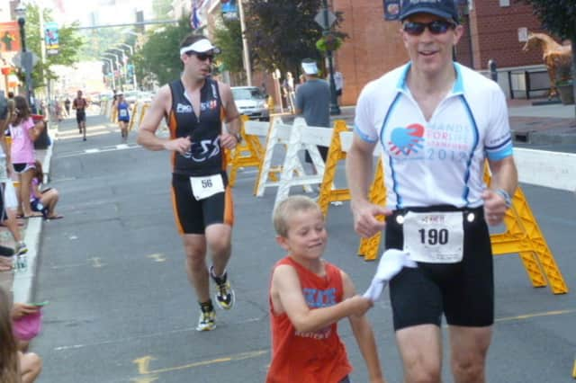 A young boy joins his father for the final stages of the Stamford KIC It Triathlon last summer.