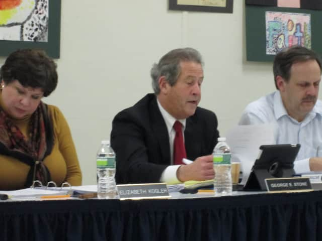Lakeland Superintendent George Stone, center, reads from the proposed policy change at Thursday night's Board of Education meeting.