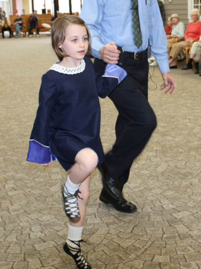Sasha Coughlin does the Irish Jig for her grandmother, Barbara Coughlin, and the rest of the community at the Village of Waveny Care Center.