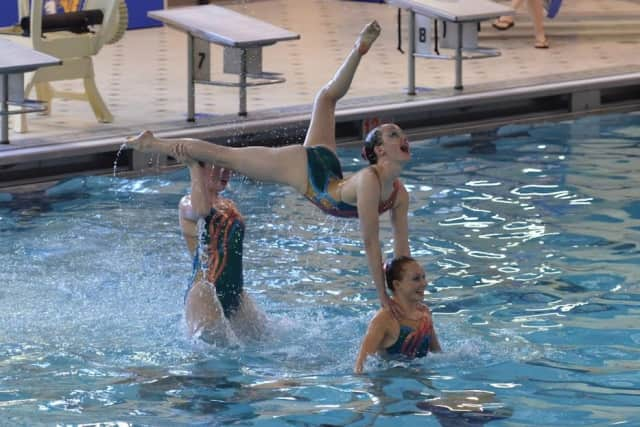 Isabella Montgomery, Renee Collett and Emily Roney of the New Canaan Aquianas execute a lift.